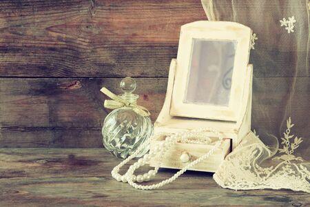 espejo: perlas vintage, antig�edad joyero de madera con espejo y frasco de perfume sobre mesa de madera. imagen filtrada
