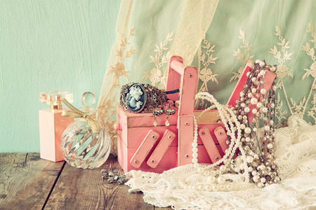 neckless: vintage jewelelry, antique wooden jewelry box  and perfume bottle on wooden table. filtered image Stock Photo