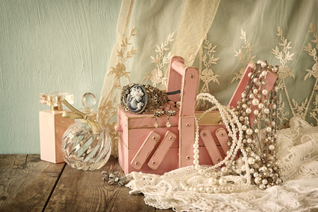 diamond necklace: vintage jewelery , antique wooden jewelery box and perfume bottle on wooden table. filtered image