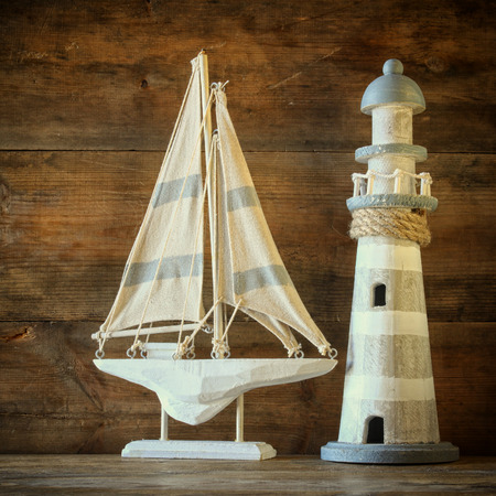 sail boat: old vintage wooden lighthouse and sailing boat on wooden table. vintage filtered image. nautical lifestyle concept