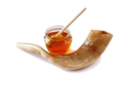 shofar: rosh hashanah jewesh holiday concept - shofar horn, honey isolated on white. traditional holiday symbols. Stock Photo