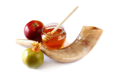 jewish food: rosh hashanah jewesh holiday concept - shofar horn, honey, apple and pomegranate isolated on white. traditional holiday symbols.