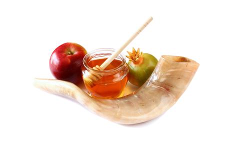 apple and honey: rosh hashanah jewesh holiday concept - shofar horn, honey, apple and pomegranate isolated on white. traditional holiday symbols.