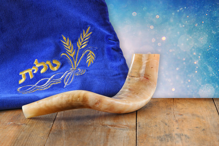 holiday symbol: image of shofar horn and prayer case with word talit prayer writen on it. room for text. rosh hashanah jewish holiday concept . traditional holiday symbol.