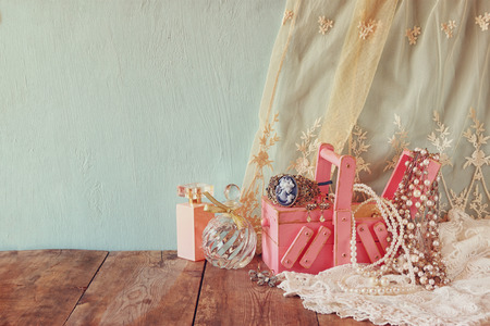 jewelry background: vintage jewelery, antique wooden jewelry box and perfume bottle on wooden table.
