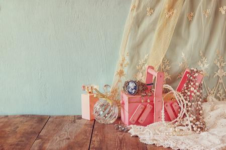 vintage juwelen, antieke houten doos juwelen en parfum fles op houten tafel.