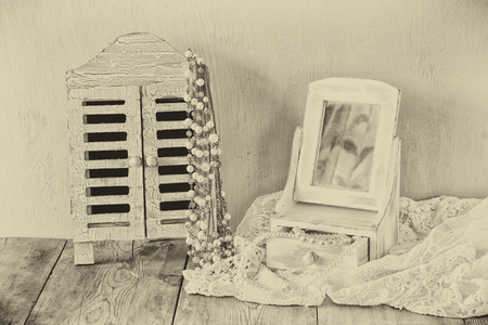 neckless: vintage pearls , antique wooden jewelry box with mirror and perfume bottle on wooden table. black and white style photo Stock Photo