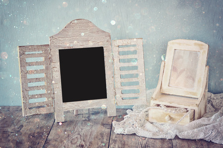 neckless: vintage pearls , antique wooden jewelry box with mirror and perfume bottle on wooden table. filtered image with glitter overlay