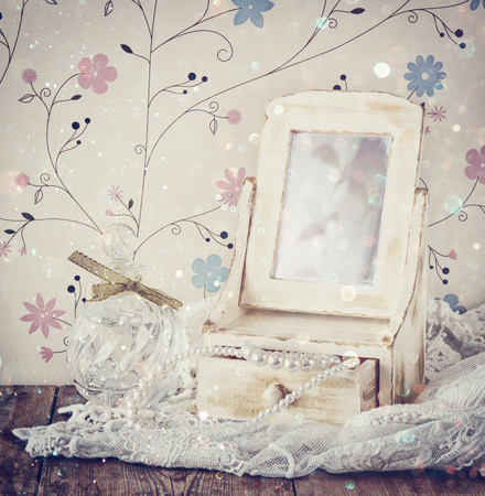antique mirror: vintage pearls , antique wooden jewelry box with mirror and perfume bottle on wooden table. filtered image with glitter overlay