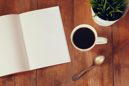 do: top view image of open notebook with blank pages next to cup of coffe on wooden table. ready for adding text or mockup Stock Photo