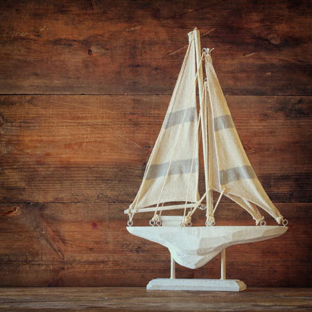 sail boat: old vintage wooden white sailing boat on wooden table. vintage filtered image. nautical lifestyle concept
