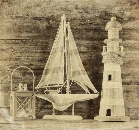 bateau voile: vieux phare et bateau à voile en bois vintage sur la table en bois. vieux style photo noir et blanc. concept de style de vie nautique