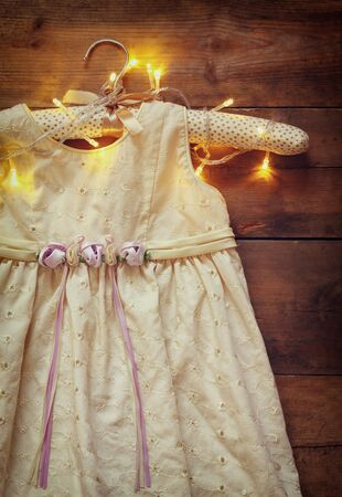 view an elegant wardrobe: vintage cream girls dress on hanger with on wooden background with garland lights Stock Photo