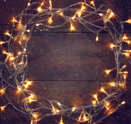 feestelijk: Kleurrijke Kerstmis warme gouden slinger lichten op houten rustieke achtergrond. gefilterde afbeelding