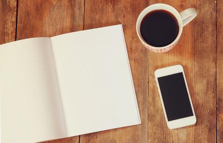 hacer: Imagen de la visión superior del cuaderno abierto con páginas en blanco junto a la taza de café y el teléfono inteligente en mesa de madera. listos para el texto o la adición de maqueta Foto de archivo