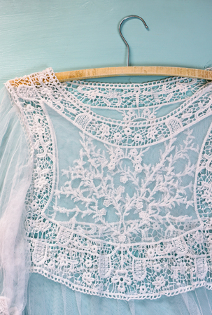 vintage background: vintage white crochet lace top with hanger on wooden background