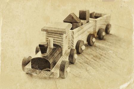 niños negros: tren de juguete de madera sobre el suelo de madera. atención selectiva. blanco y negro vieja foto de estilo