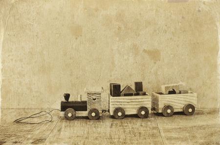 juguetes antiguos: tren de juguete de madera sobre la mesa de madera. blanco y negro vieja foto de estilo Foto de archivo