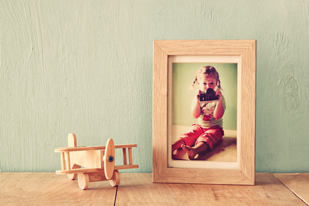 old frame: wooden airplane toy over wood table next to photo frame with kids old photography. retro filtered image