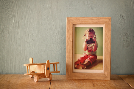 plane table: wooden airplane toy over wood table next to photo frame with kids old photography. retro filtered image