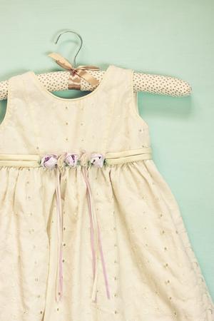 view an elegant wardrobe: vintage cream girls dress on hanger with on wooden background