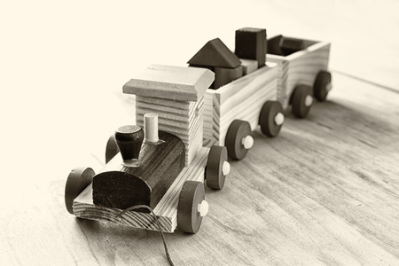 black train: Wooden toy train over wooden floor. selective focus. black and white old style photo Stock Photo