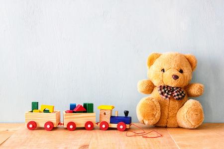 Tren de juguete de madera y oso de peluche sobre el piso de madera. retro filtrada Foto de archivo - 44055803