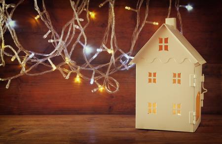 licht: weiße Haus Laterne mit brennenden Kerzen im Inneren vor girlande gold Lichter auf Holztisch. retro gefilterte Bild