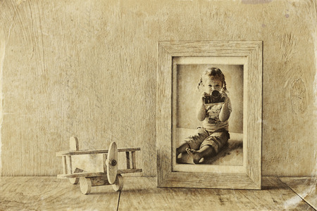 black and white photography: wooden airplane toy over wood table next to photo frame with kids old photography. black and white style photo