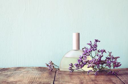 inodoro: nueva botella de perfume de la vendimia lado de las flores aromáticas en la mesa de madera. retro imagen filtrada