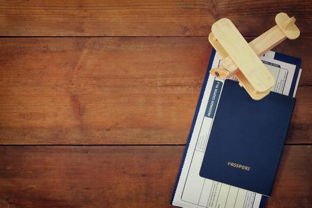 top beeld van vliegende ticket houten vliegtuig en paspoort over houten tafel view