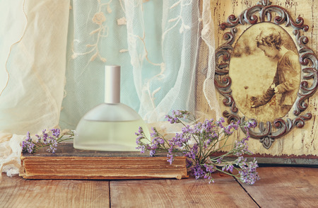 fresh vintage perfume bottle next to aromatic flowers and antique frame with old photography on wooden table. retro filtered image