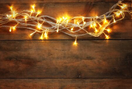 abstract photo of Christmas warm gold garland lights on wooden rustic background. filtered image Stock Photo