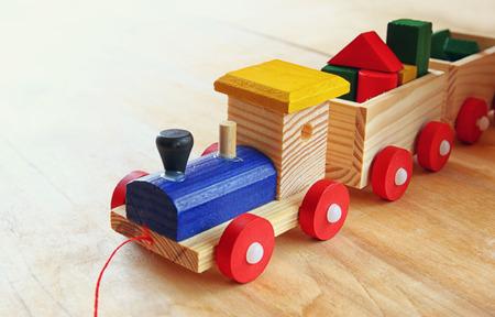 niños felices: cerca del tren de juguete de madera sobre la mesa de madera. atención selectiva. retro filtrada Foto de archivo