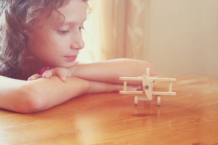 abstract photo of cute kid looking at old wooden plane. selective focus