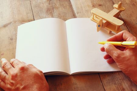 open hands: open blank notebook and man hands next to toy aeroplane on wooden table. retro style  filtered image