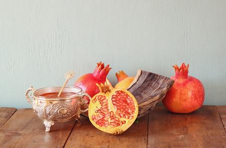 shofar: rosh hashanah jewesh holiday concept - shofar, honey, apple and pomegranate over wooden table. traditional holiday symbols. Stock Photo