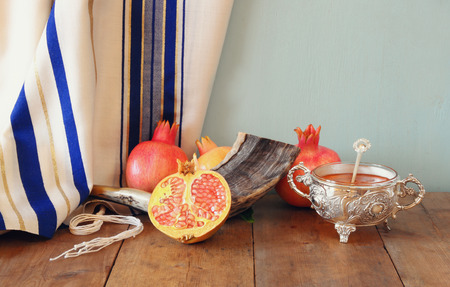 top year: rosh hashanah jewesh holiday concept - shofar, honey, apple and pomegranate over wooden table. traditional holiday symbols. Stock Photo