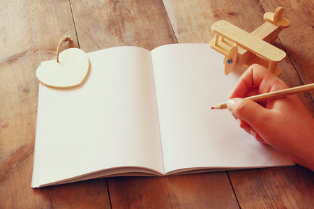 aeroplane: open blank notebook over wooden table. ready for mockup. retro filtered image Stock Photo