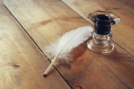 piuma bianca: Foto di penna e calamaio sul vecchio tavolo di legno. immagine filtrata retrò