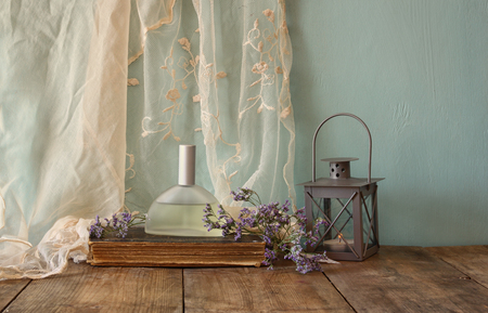 dressing: fresh vintage perfume bottle next to aromatic flowers on wooden table. retro filtered image Stock Photo