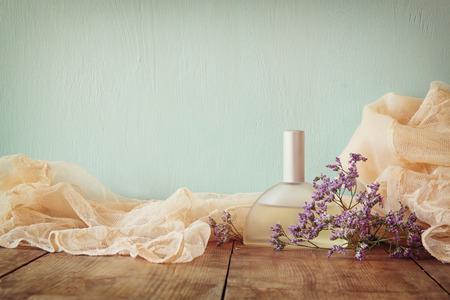 나무 테이블에 향기로운 꽃 옆에 신선한 빈티지 향수 병. 복고풍 필터링 된 이미지 스톡 콘텐츠