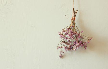 bouquet de fleurs: bouquet de fleurs séchées suspendus sur corde contre fond en bois