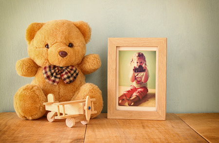 wooden airplane toy and teddy bear over wood table next to photo frame with kids old photography. retro filtered image