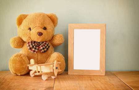 blank photo: wooden airplane toy and teddy bear over wood table next to blank photo frame. retro filtered image. ready to place photography