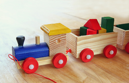 wooden toy: close up of Wooden toy train over wooden table. selective focus. retro filtered