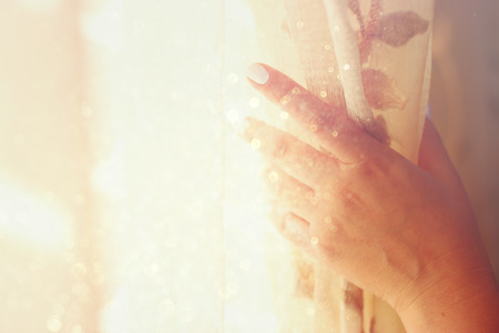 woman's hand opening curtains in a bedroom. natural light burst. filtered image with selective focus