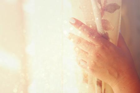 adentro y afuera: la apertura de la mano de la mujer cortinas en un dormitorio. explosión de la luz natural. imagen filtrada con el enfoque selectivo