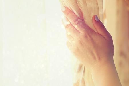 cortinas: la apertura de la mano de la mujer cortinas en un dormitorio. explosión de la luz natural. imagen filtrada con el enfoque selectivo