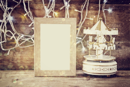 blank photo: abstract image of old vintage white carousel horses with garland gold lights and blank frame on wooden table. retro filtered image Stock Photo